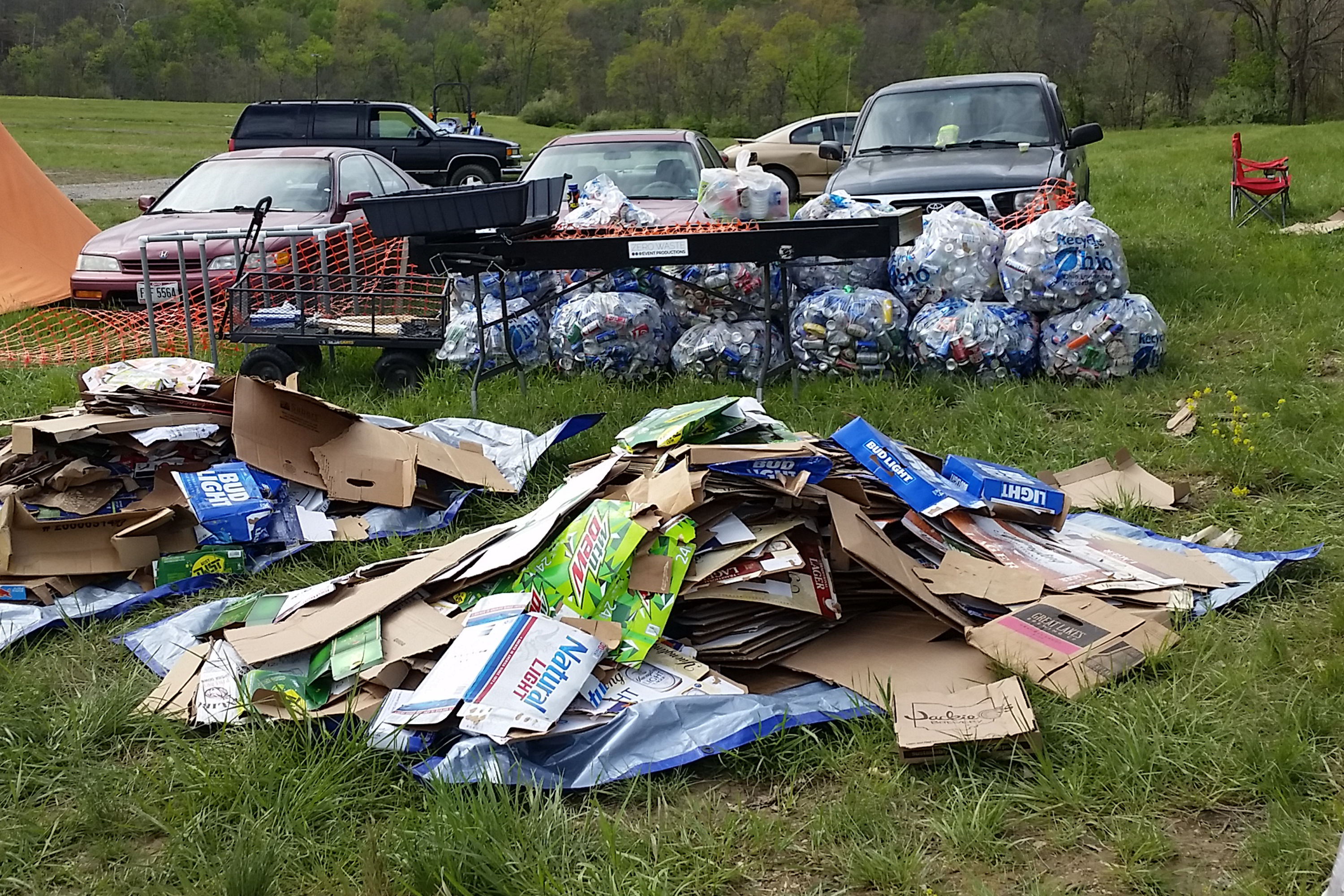 A pile of cardboard in front of a pile of sorted cans at #Fest.
