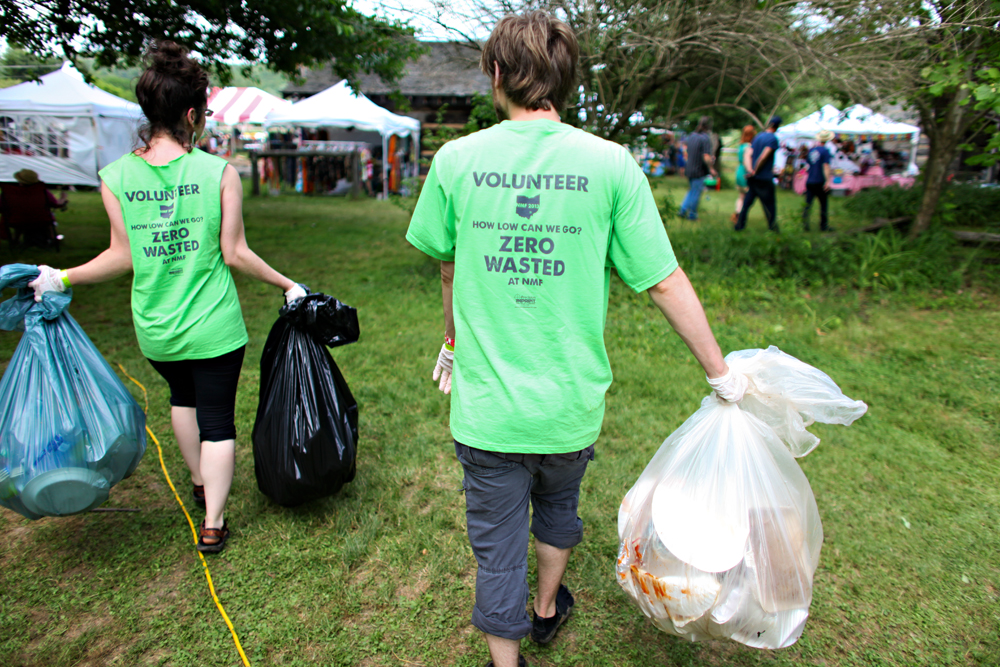 Volunteers carry recycling, compost, and trash bags back to the Zero Waste Event Productions tent in 2013.
