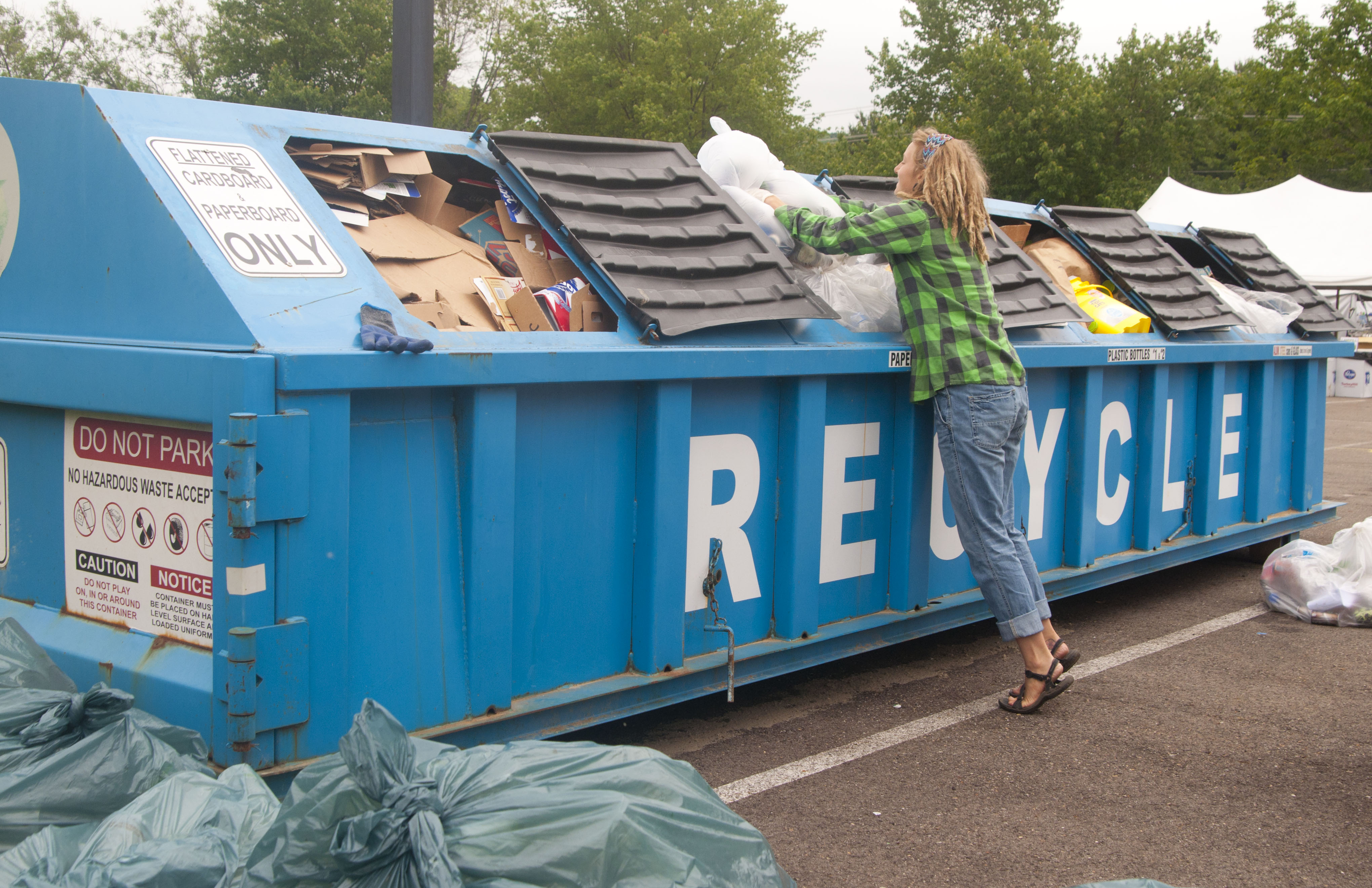 A volunteers adds recycling to a roll off at Nelsonville Music Festival.