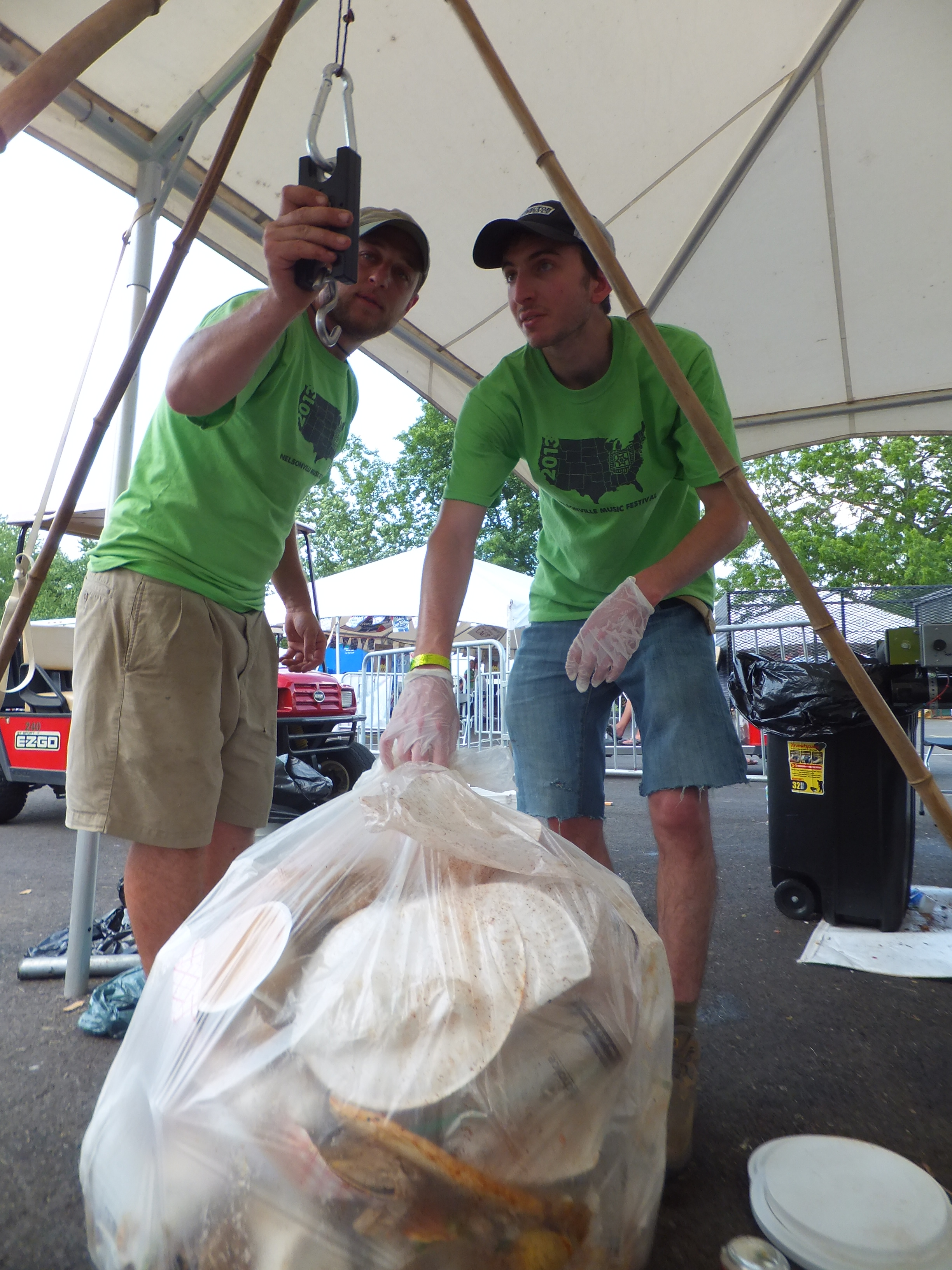 A staffer teaches a volunteer how to weight compostable materials at Nelsonville Music Festival, 2014.