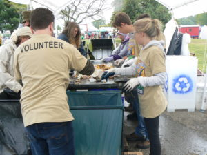 Volunteer sort recycling and compost on a mobile conveyor belt at the Ohio Pawpaw Festival in 2016.